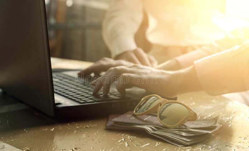 Le mani sulla tastiera del computer portatile, la donna nei precedenti, soldi degli uomini hanno investito in passaporto ed occhi immagini stock libere da diritti