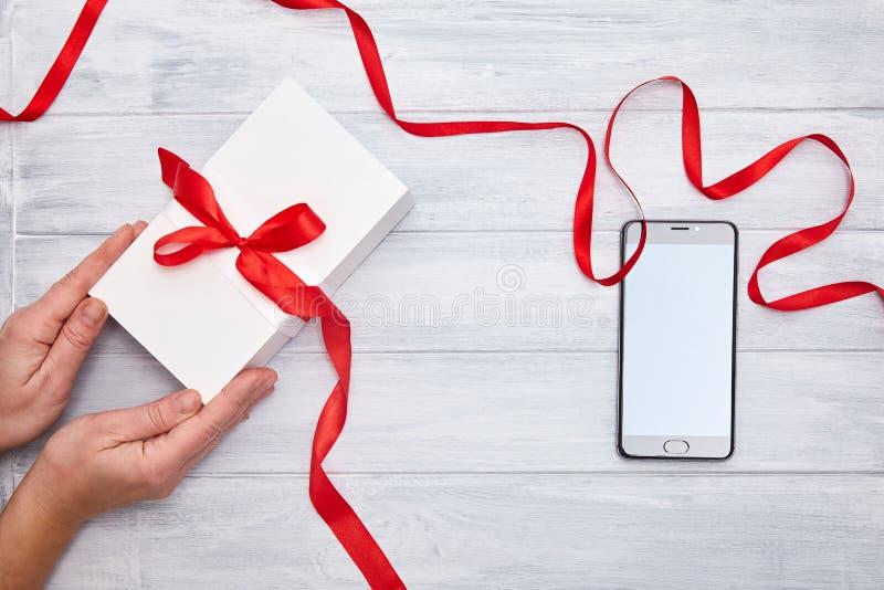 Le mani tengono il contenitore di regalo con il nastro rosso e lo smartphone su un fondo del woodem fotografia stock libera da diritti