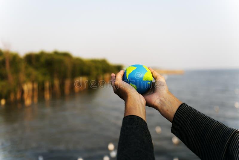 Le mani tengono l'ecologia verde globale dell'ambiente immagine stock