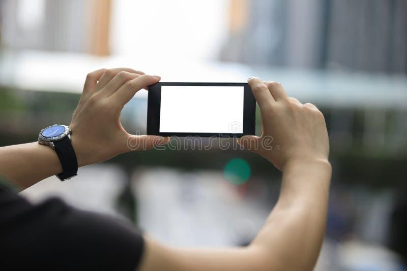 Le mani tengono lo smartphone prendono le immagini fotografia stock libera da diritti