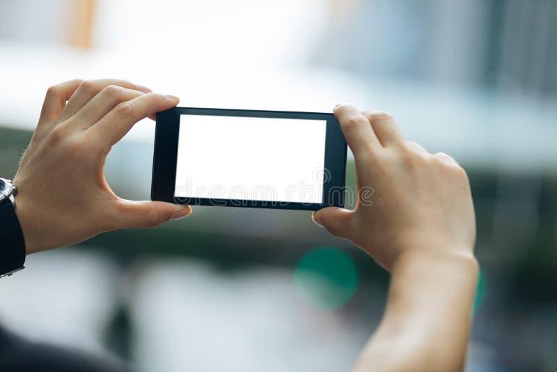 Le mani tengono lo smartphone prendono le immagini immagini stock