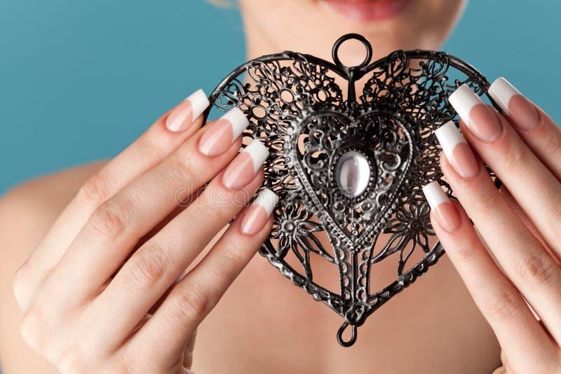 Le mani umane con il bello manicure tengono un cuore openwork fotografia stock libera da diritti