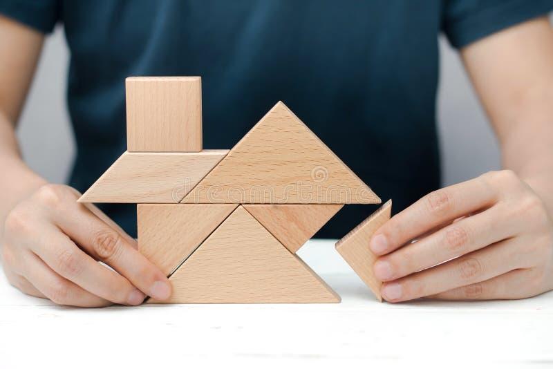 Le mani umane provano a sviluppare la casa o la casa con il puzzle di legno del tangram fotografia stock