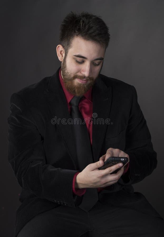 Le mannen i formell dress med telefonen royaltyfri foto
