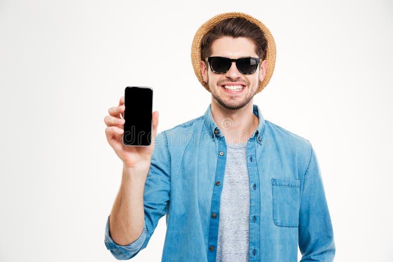 Le mannen i hatten och solglasögon som rymmer smartphonen för tom skärm royaltyfri bild