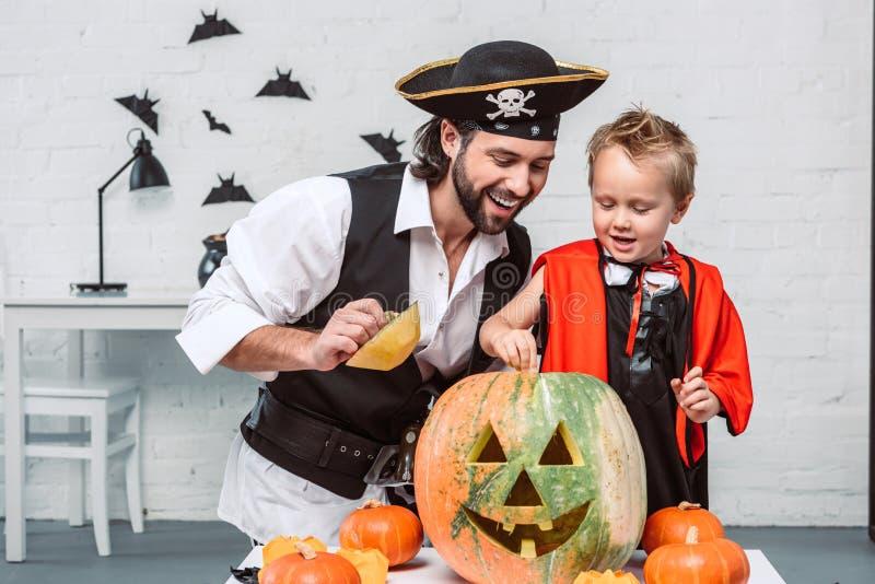 le mannen i piratkopiera dräkten och sonen i den vampyrhalloween dräkten som tillsammans ser in i pumpa arkivbilder