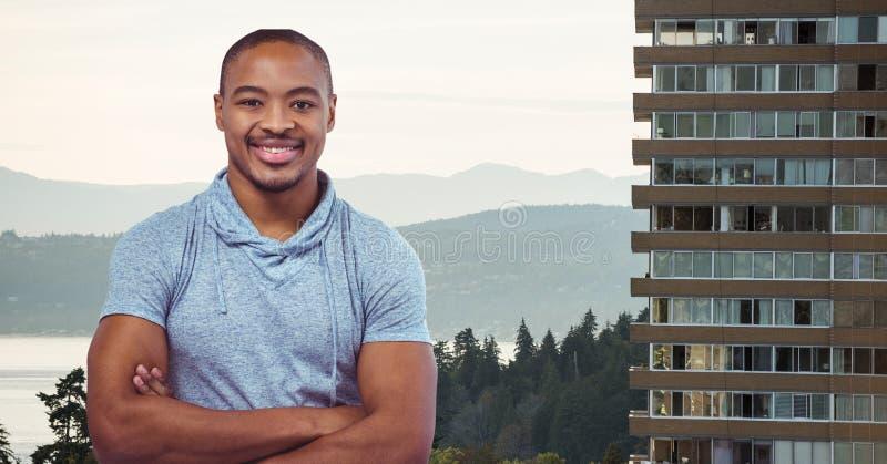 Le mannen med armar korsade mot berg och byggande royaltyfri bild