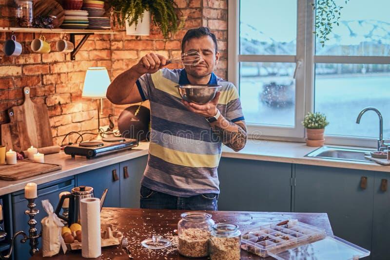 Le mannen med en tatuering på hans hand som rymmer en bunke och inhalation av aromen av mat i köket royaltyfri foto