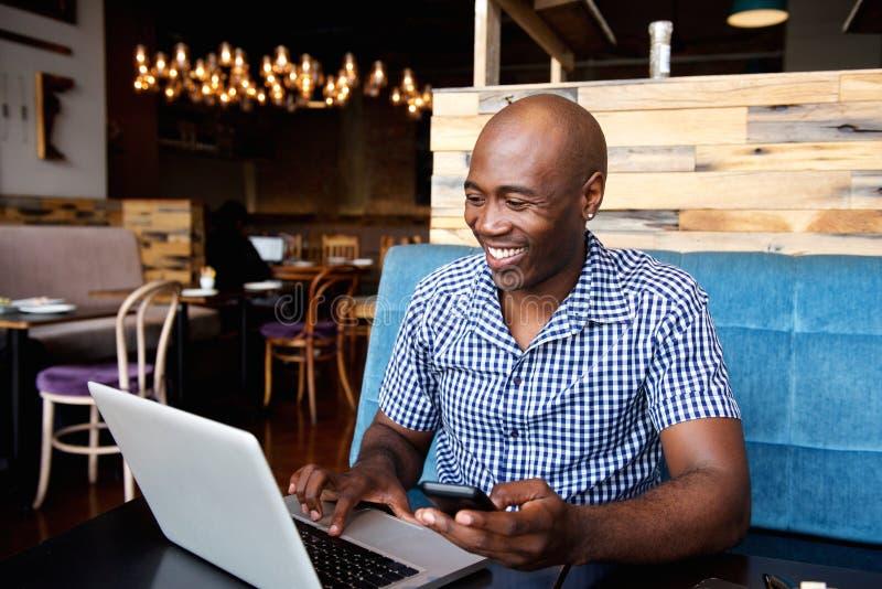Le mannen med ett mobiltelefonsammanträde på kafét genom att använda bärbara datorn arkivfoto