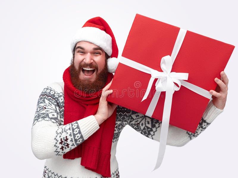 Le mannen med ett skägg som rymmer den röda julasken royaltyfria foton