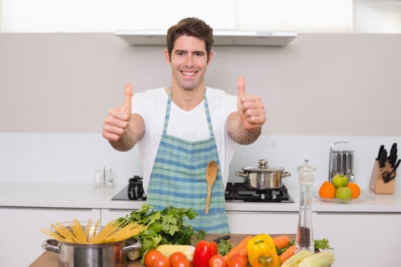 Le mannen med grönsaker som gör en gest tummar upp i kök arkivfoto