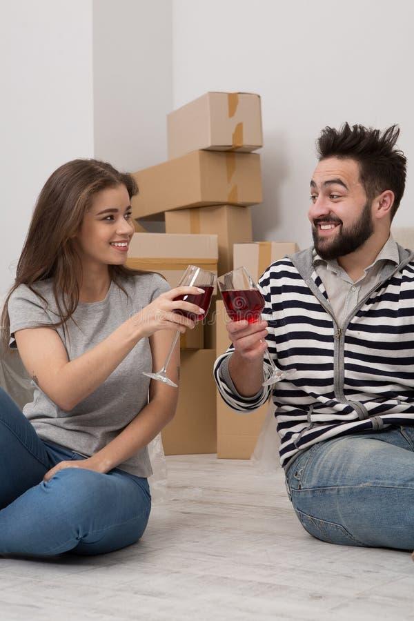 Le mannen och kvinnan som dricker vin för att fira det köpande nya hemmet royaltyfri foto