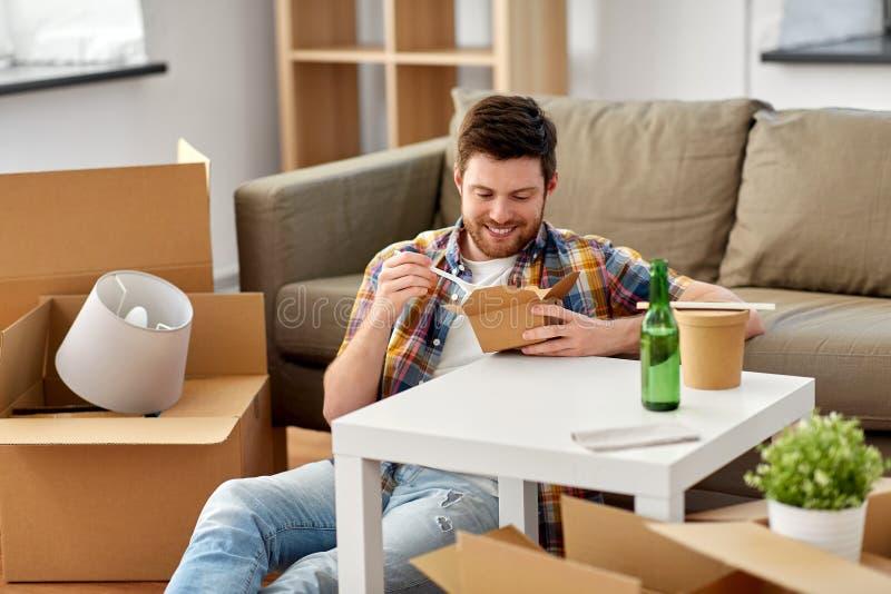 Le mannen som äter takeaway mat på det nya hemmet royaltyfri bild
