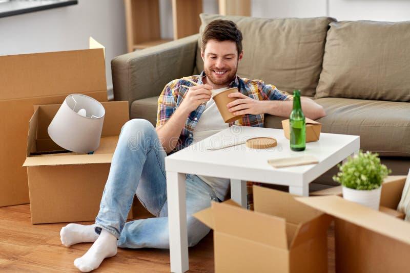 Le mannen som äter takeaway mat på det nya hemmet arkivbilder