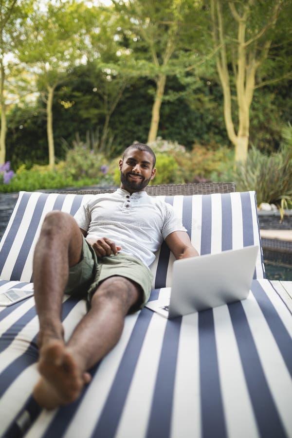 Le mannen som använder bärbara datorn, medan koppla av på vardagsrumstol på farstubron fotografering för bildbyråer