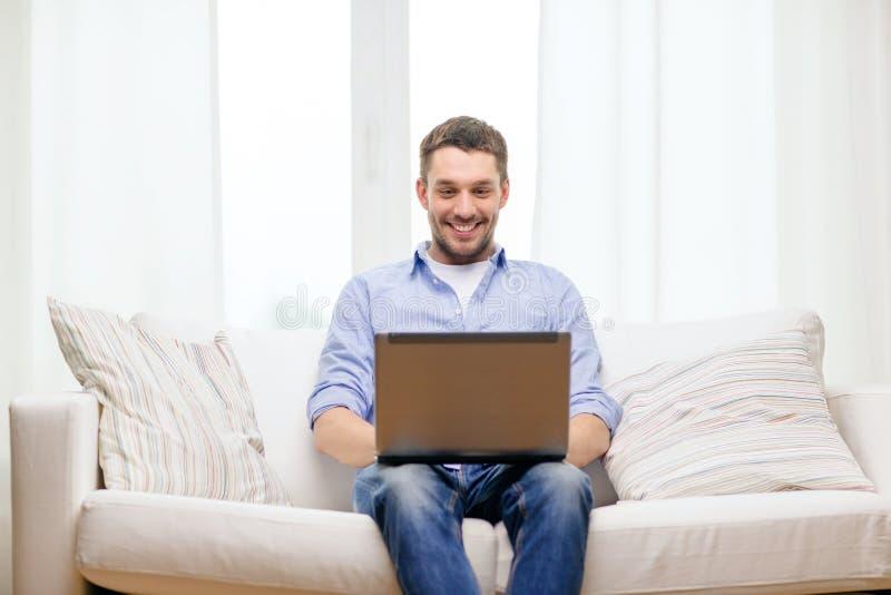 Le mannen som arbetar med den hemmastadda bärbara datorn royaltyfri foto