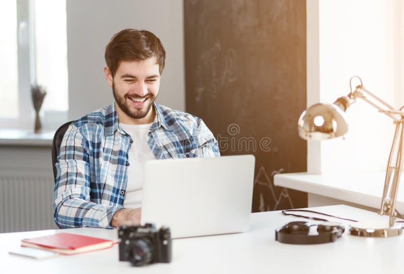 Le mannen som arbetar på bärbara datorn på tabellen royaltyfri fotografi