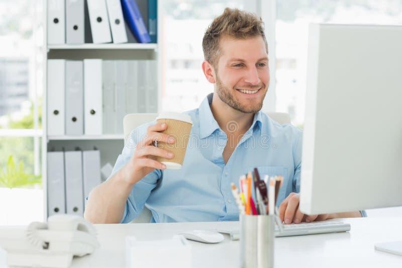 Le mannen som arbetar på hans skrivbord som dricker ett bort kaffe för tagande arkivbilder