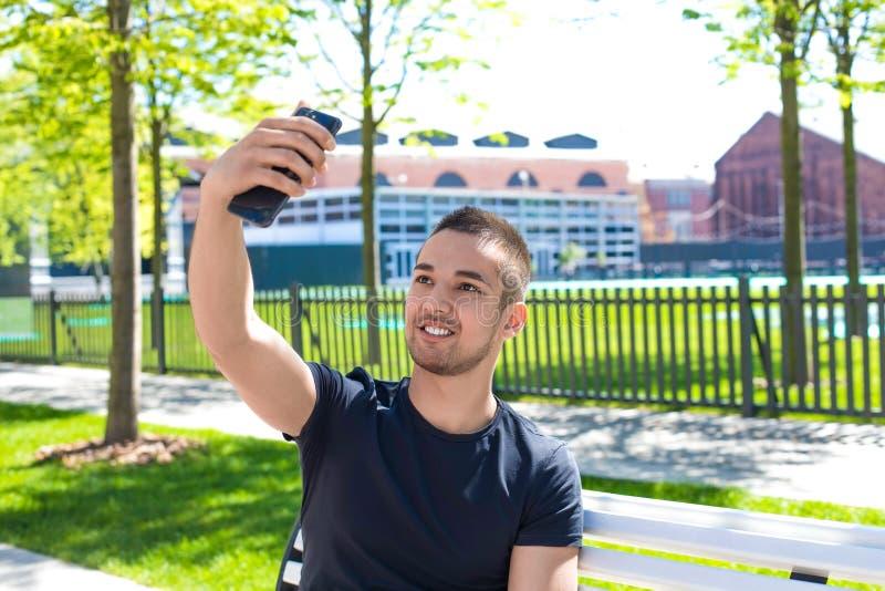 Le mannen som har online-video appell på smartphonen under fri tid utomhus royaltyfria bilder
