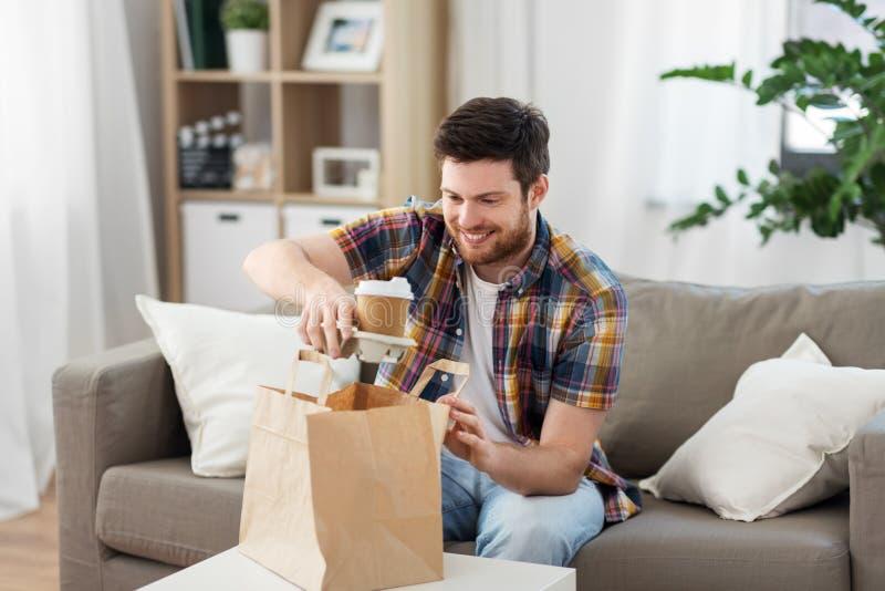 Le mannen som hemma packar upp takeaway mat arkivbild