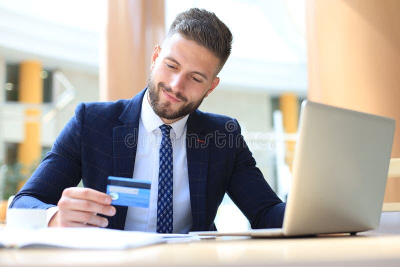 Le mannen som i regeringsst?llning sitter, och l?ner vid kreditkorten med hans b?rbar dator royaltyfria bilder