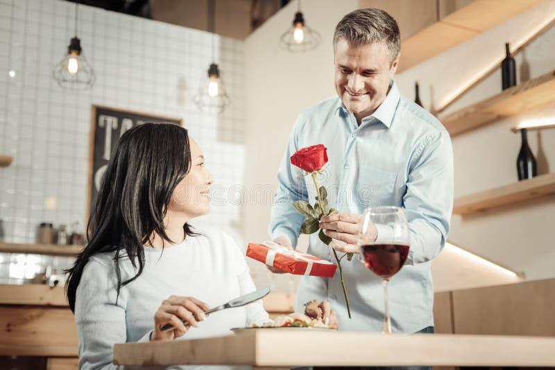 Le mannen som kommer med blomman och godisar royaltyfri fotografi