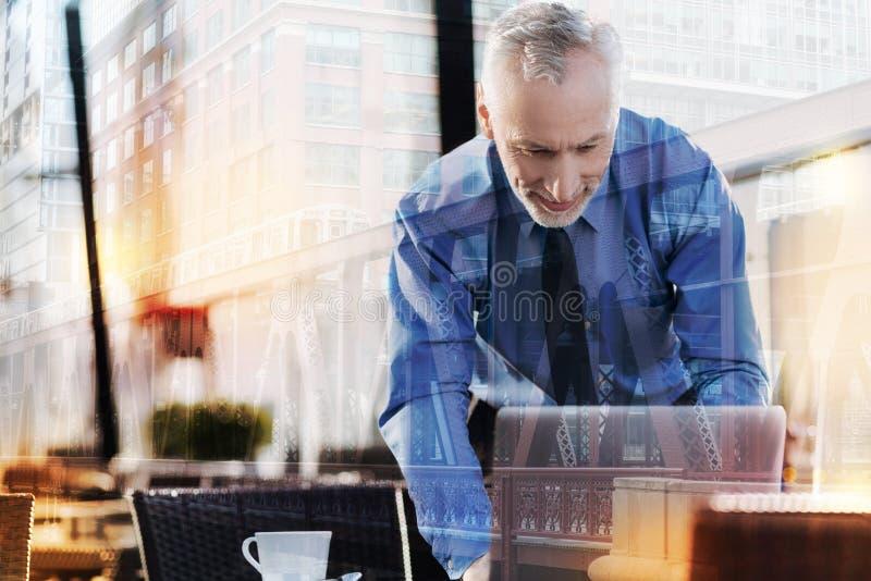 Le mannen som lutar till hans bärbar dator, medan vara i ett kafé arkivfoto