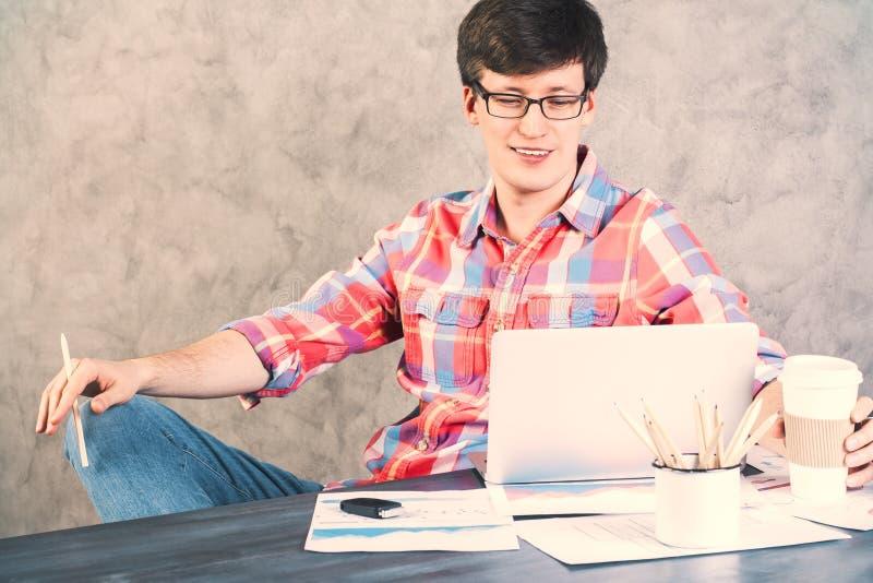 Le mannen som ser bärbara datorn royaltyfri bild