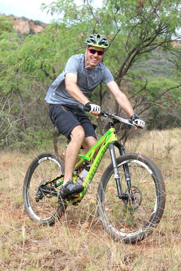 Le mannen som utomhus tycker om ritt på mountainbikeloppet royaltyfri foto