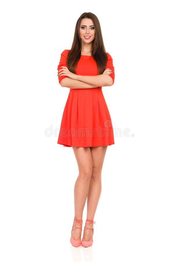Le mannequin In Red Mini Dress And High Heels se tient avec des bras croisés photo libre de droits