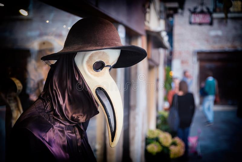 Le mannequin vénitien traditionnel dans le costume de docteur de peste, le masque et le chapeau près font des emplettes fenêtre d photos stock