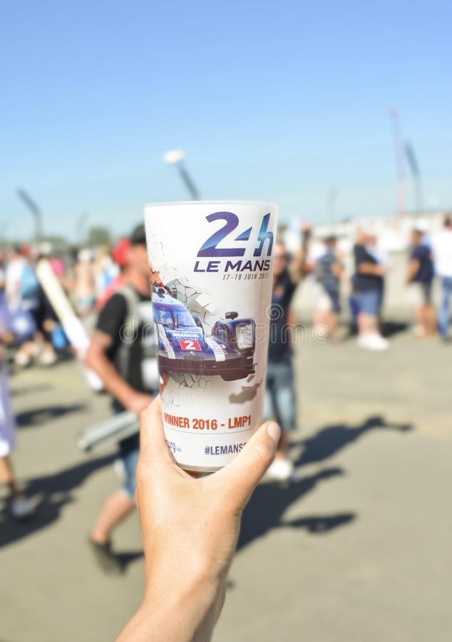 LE MANS, FRANCE - JUNE 18, 2017: A hand holds a plastic glass with beer with a photo of winner's car during race 24 hours. Of Le mans stock photography