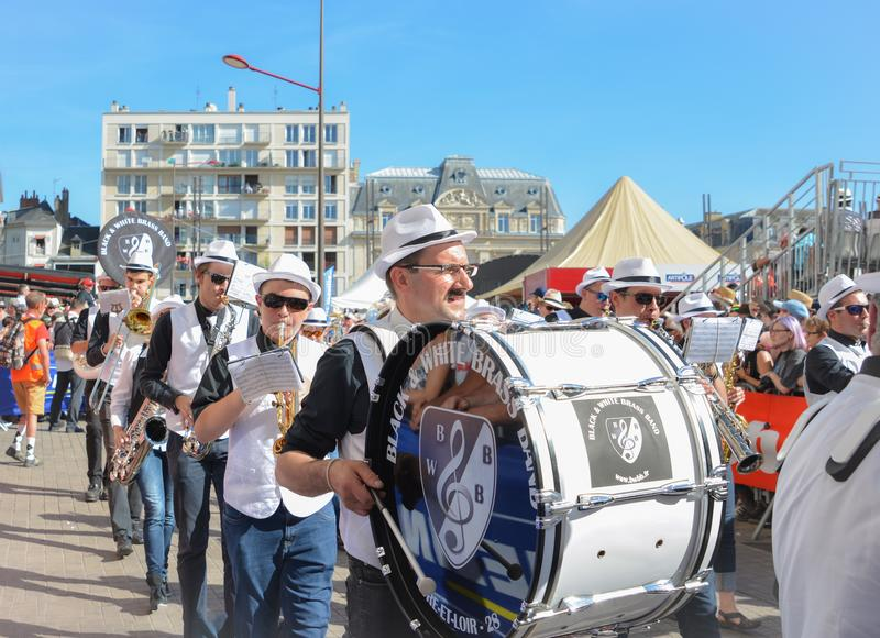 LE MANS, FRANCE - JUNE 16, 2017:Orchestra with various musical instruments marching band during parade of pilots racing in Le mans. LE MANS, FRANCE - JUNE 16 stock image