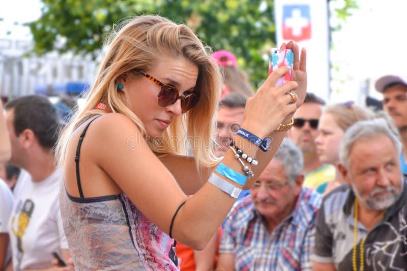 LE MANS, FRANCIA - 13 GIUGNO 2014: La bella ragazza fa l'autoritratto sullo smartphone circondato dall'uomo immagine stock