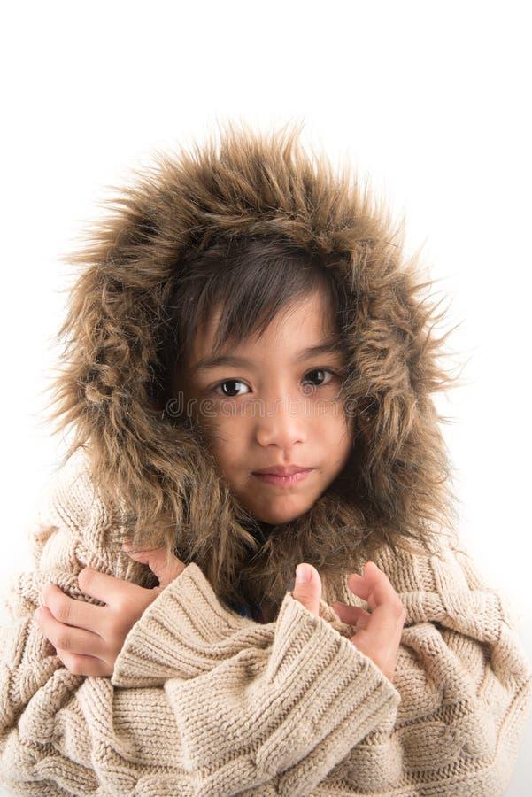 Le manteau de fourrure de port de petit garçon se protègent contre des frais généraux froids de neige photographie stock libre de droits