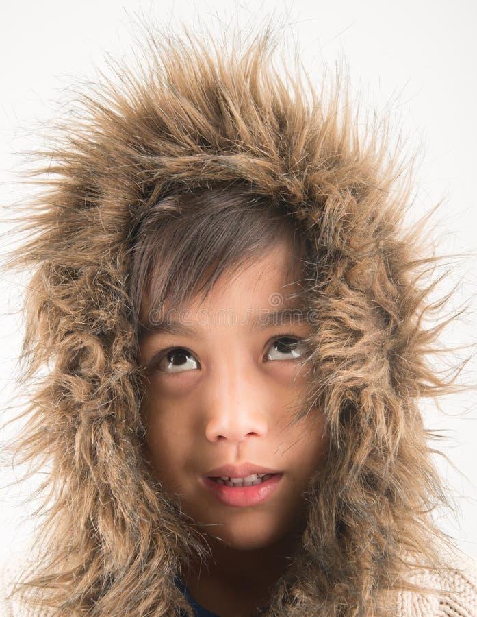 Le manteau de fourrure de port de petit garçon se protègent contre des frais généraux froids de neige photos stock