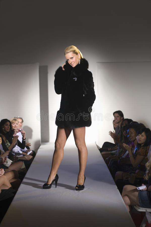 Le manteau de fourrure modèle d'In Short Black se tient sur la passerelle de mode photos stock