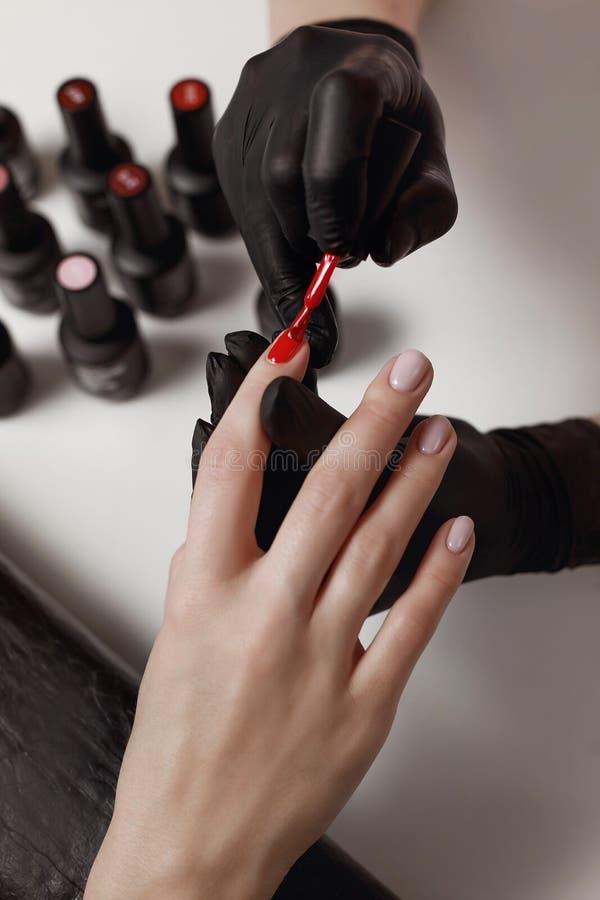 Le manucure dans les gants noirs, cause le gel de client polonais image stock