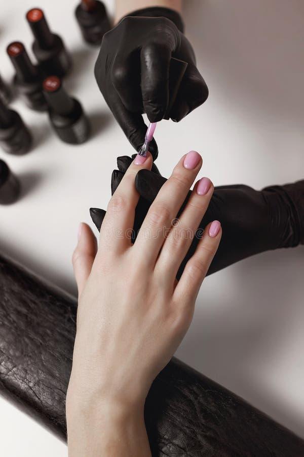 Le manucure dans les gants noirs, cause le gel de client polonais photographie stock