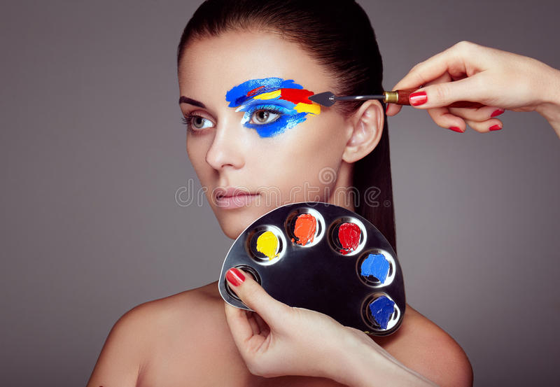 Le maquilleur applique le maquillage coloré photos stock