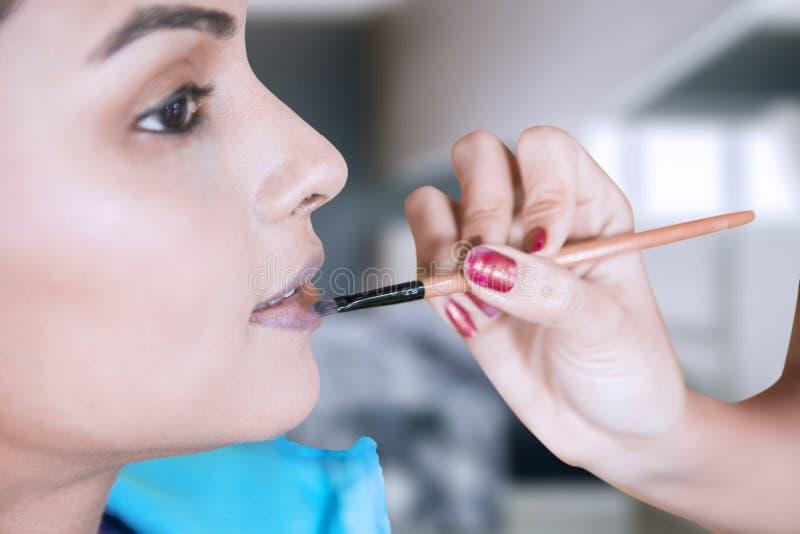 Le maquilleur applique le rouge à lèvres sur ses lèvres modèles images libres de droits