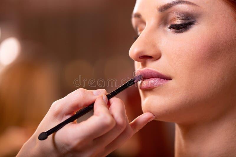 Le maquilleur applique le rouge ? l?vres rouge Beau visage de femme Main du ma?tre de maquillage, l?vres de peinture de jeune mod photos stock