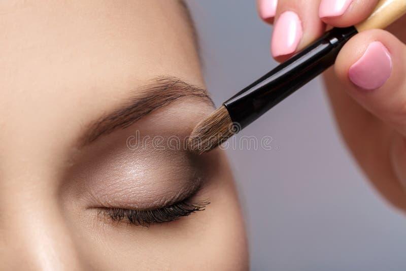 Le maquilleur appliquent la brosse de maquillage pour des yeux maquillage pour la jeune fille Fard à paupières de Brown Fin vers  image libre de droits