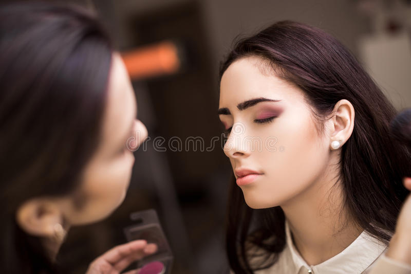 Le maquilleur appliquent le maquillage image stock