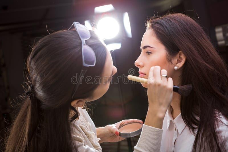Le maquilleur appliquent le maquillage photographie stock libre de droits