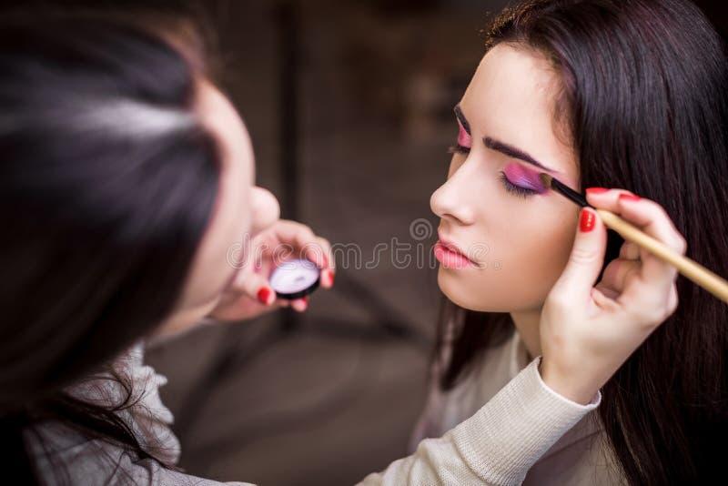 Le maquilleur appliquent le maquillage photos libres de droits