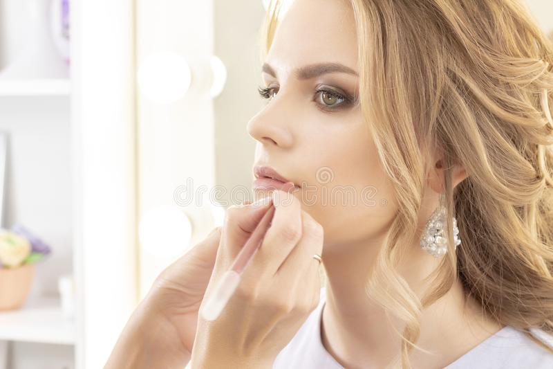 Le maquilleur peint des lèvres modèlent avec le revêtement de lèvre maquillage aux nuances beiges neutres de jour doux photos libres de droits