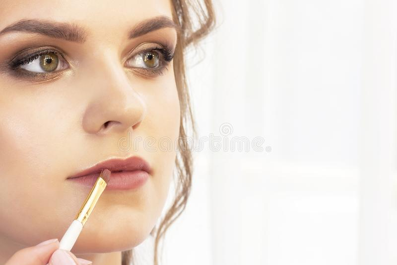 Le maquilleur s'applique le maquillage au mod?le pinceau de lèvre pour le rouge à lèvres beau modèle de fille, portrait Couleurs  image libre de droits
