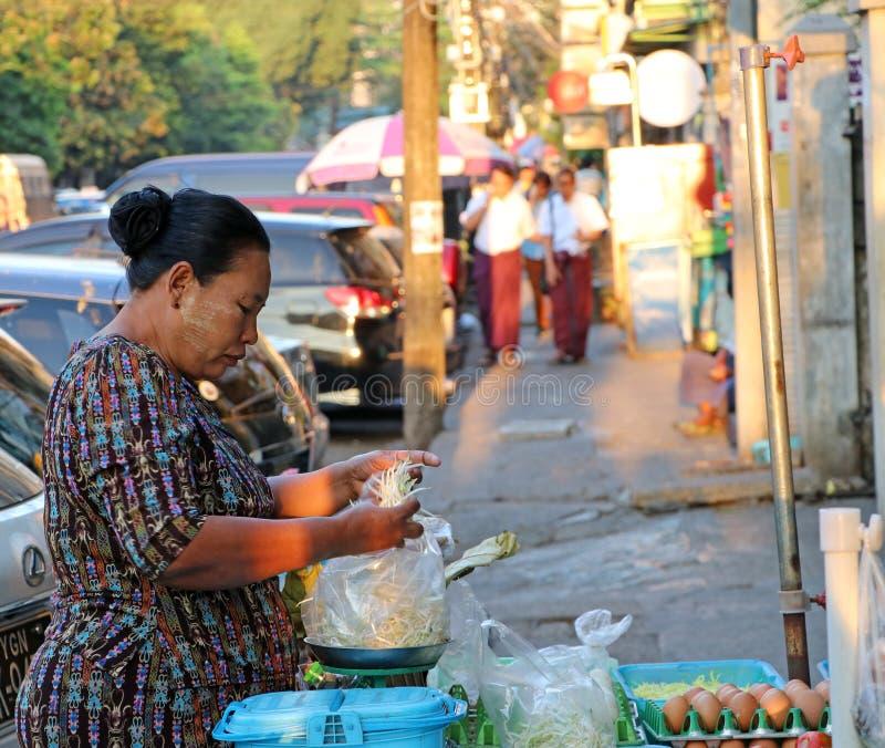 Le marchand ambulant féminin de Myanmese vendant le légume pèse des pousses de haricot à son magasin près de route à Yangon images libres de droits