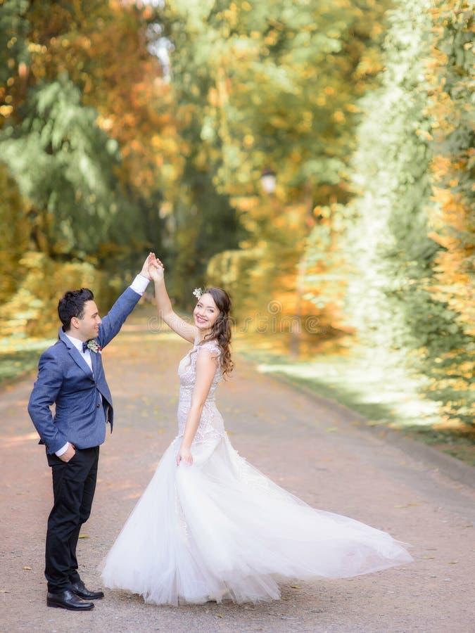 Le marié élégant dans la veste bleue tourbillonne la jeune mariée heureuse en parc d'automne images libres de droits